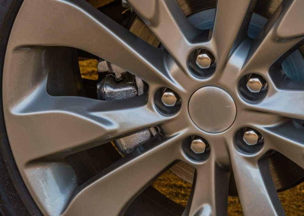 Closeup of lug nuts on a shiny chrome aluminum wheel.