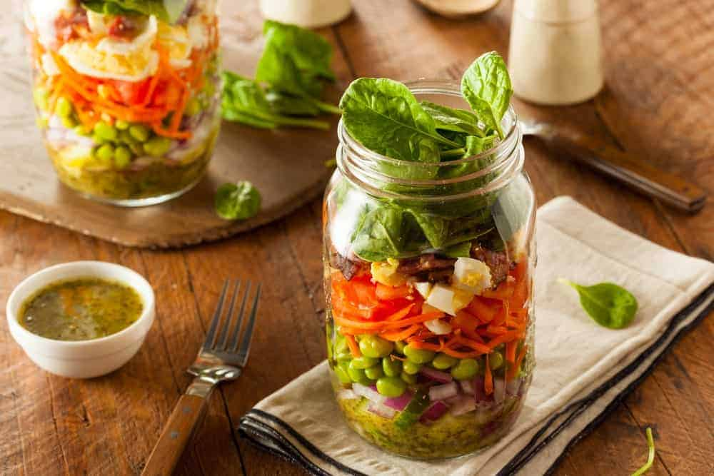 Mason jars filled with vegetable salad.
