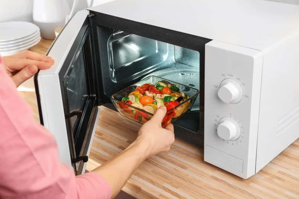 Placing or removing a dish in the microwave.