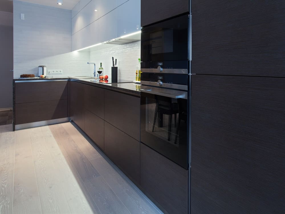 Minimalist l-shaped black kitchen with some white upper cabinets.