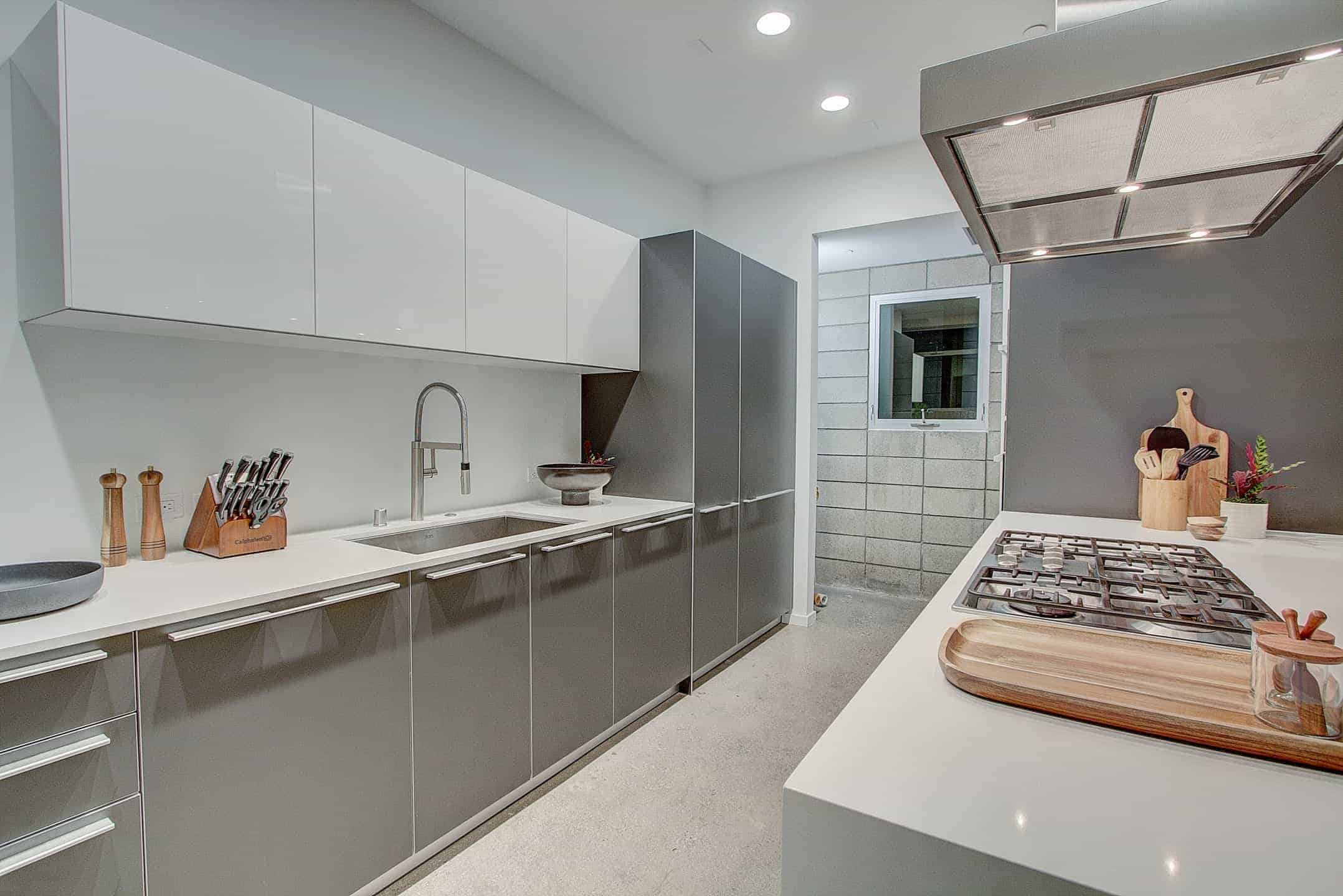 A kitchen featuring gray kitchen counters and center island both with smooth white countertops and lighted by recessed ceiling lights.
