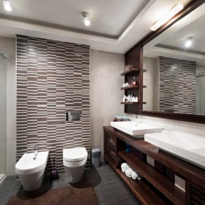 Masculine modern primary bathroom with accent wall, dark flooring, dark wood vanity with white basin sinks.