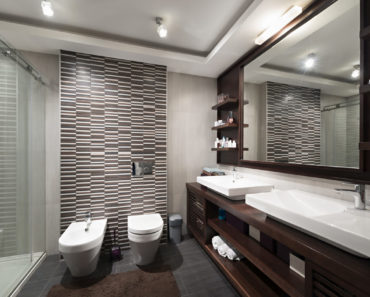 Masculine modern master bathroom with accent wall, dark flooring, dark wood vanity with white basin sinks.