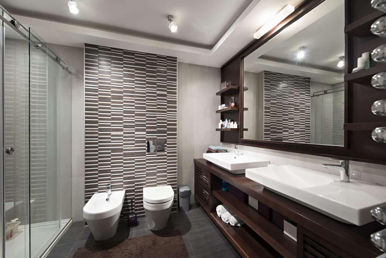 Masculine modern primary bathroom with accent wall, dark flooring, dark wood vanity with white basin sinks.