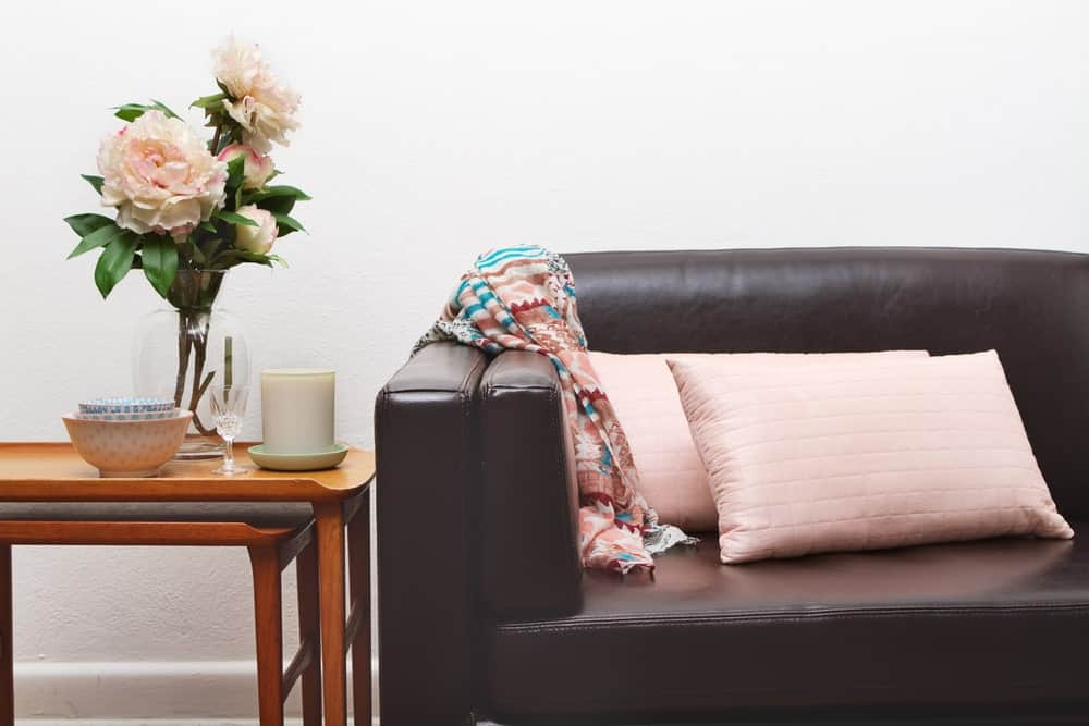 A vase of flowers and other trinkets stand on the nesting tables beside the leather sofa with throw blanket and pillows.
