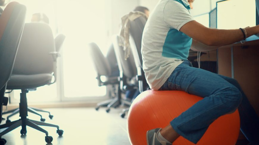 An employee sits on a fitness ball while working as a healthy alternative to office chairs.