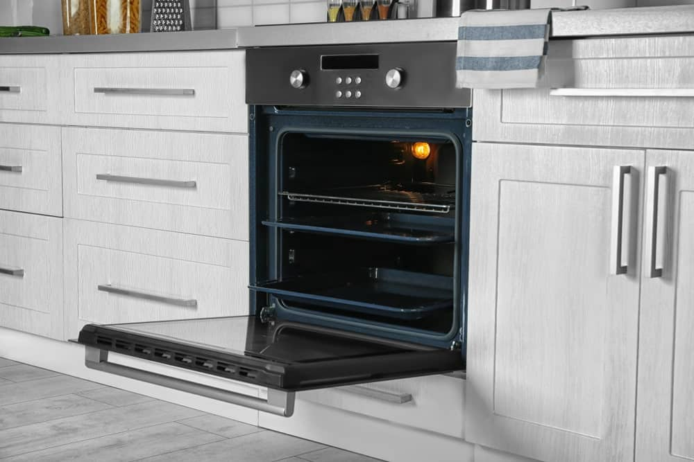 An empty oven in the kitchen left wide open.