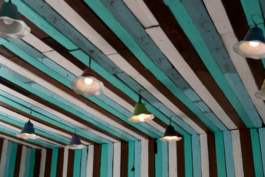 Painted wood plank ceiling with pendant lighting.