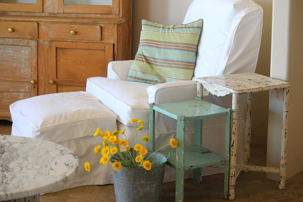 A recliner chair and ottoman covered in white slipcover with a throw pillow beside a pair of painted side tables and a bucket of flowers.