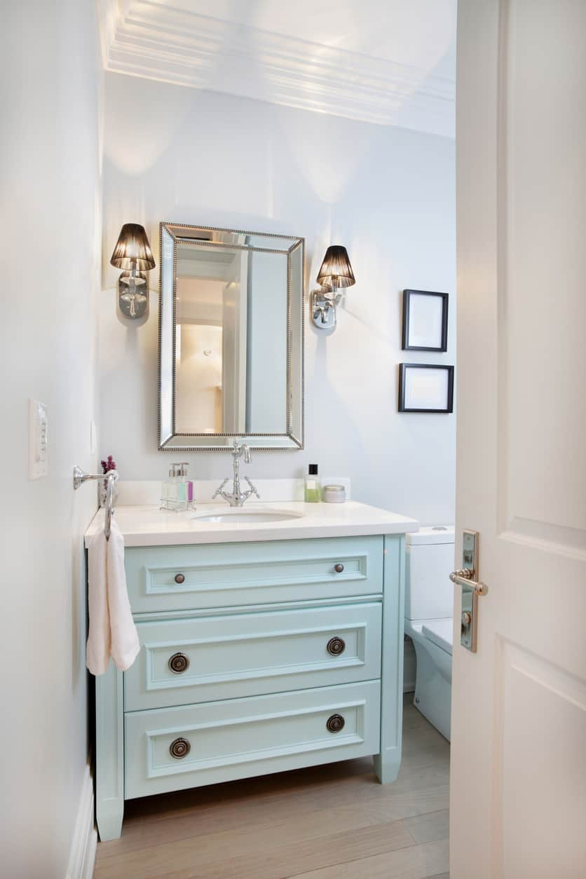Transitional powder room with light blue dresser style vanity in otherwise all white powder room except for the very light wood flooring.