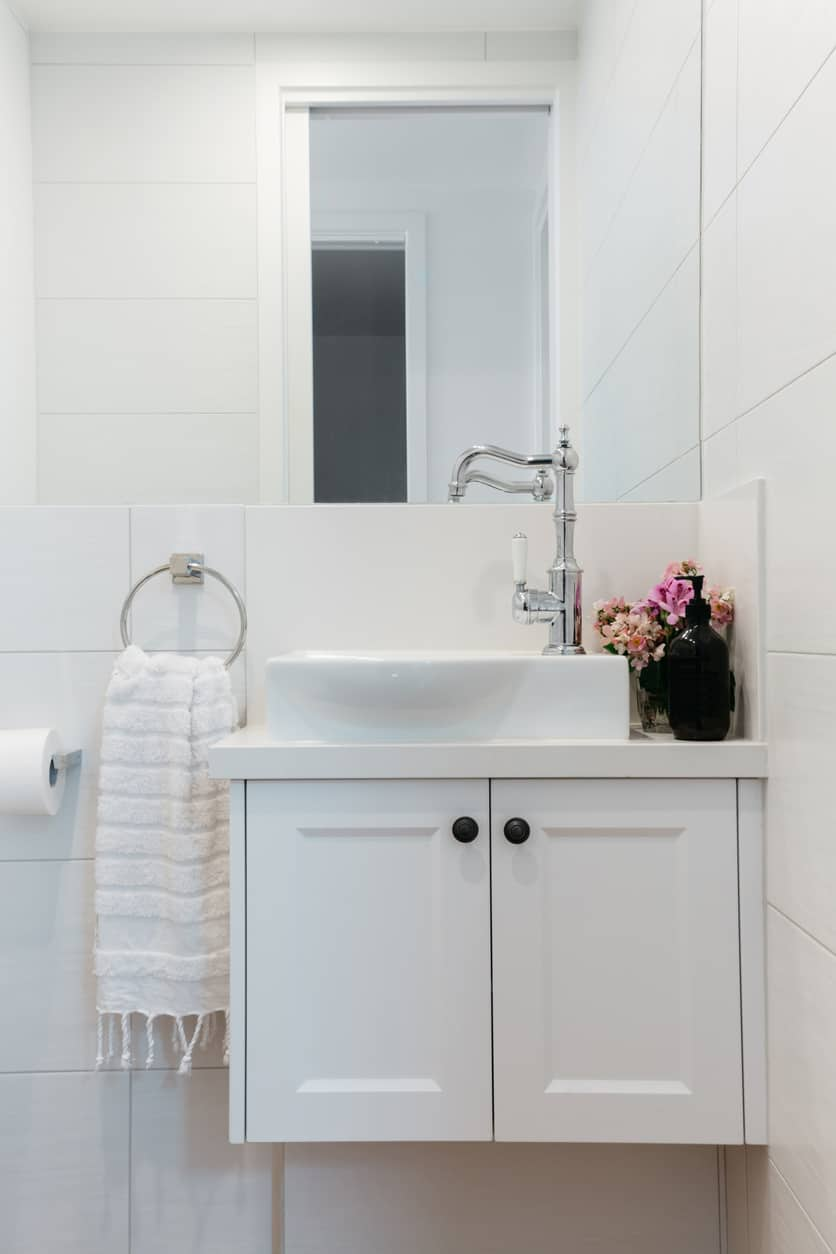 Bright white powder room with floating white vanity, white vessel sink and white tile walls.