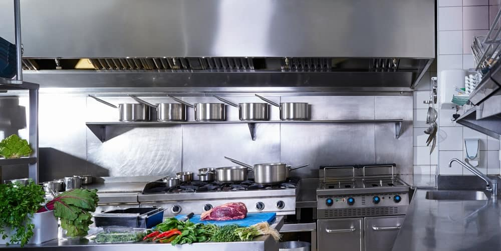 Professional stainless steel kitchen with pots displayed on a single ledge above the cooking area.
