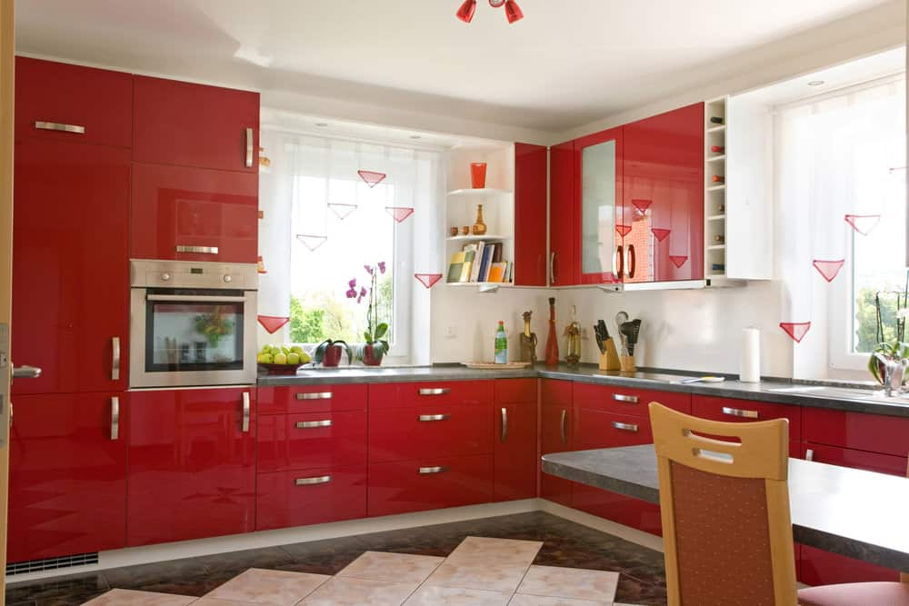 L-shaped kitchen with modern glossy red kitchen cabinets, gray countertops and white walls. I think the floor should be white as well.