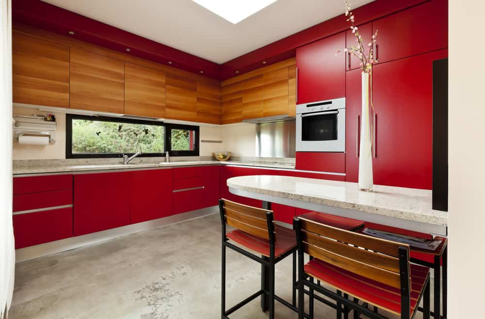 Minimalist kitchen design with modern red cabinets as well as natural wood cabinets. I think the wood cabinets make the design confusing. It would be better either all wood or all red.