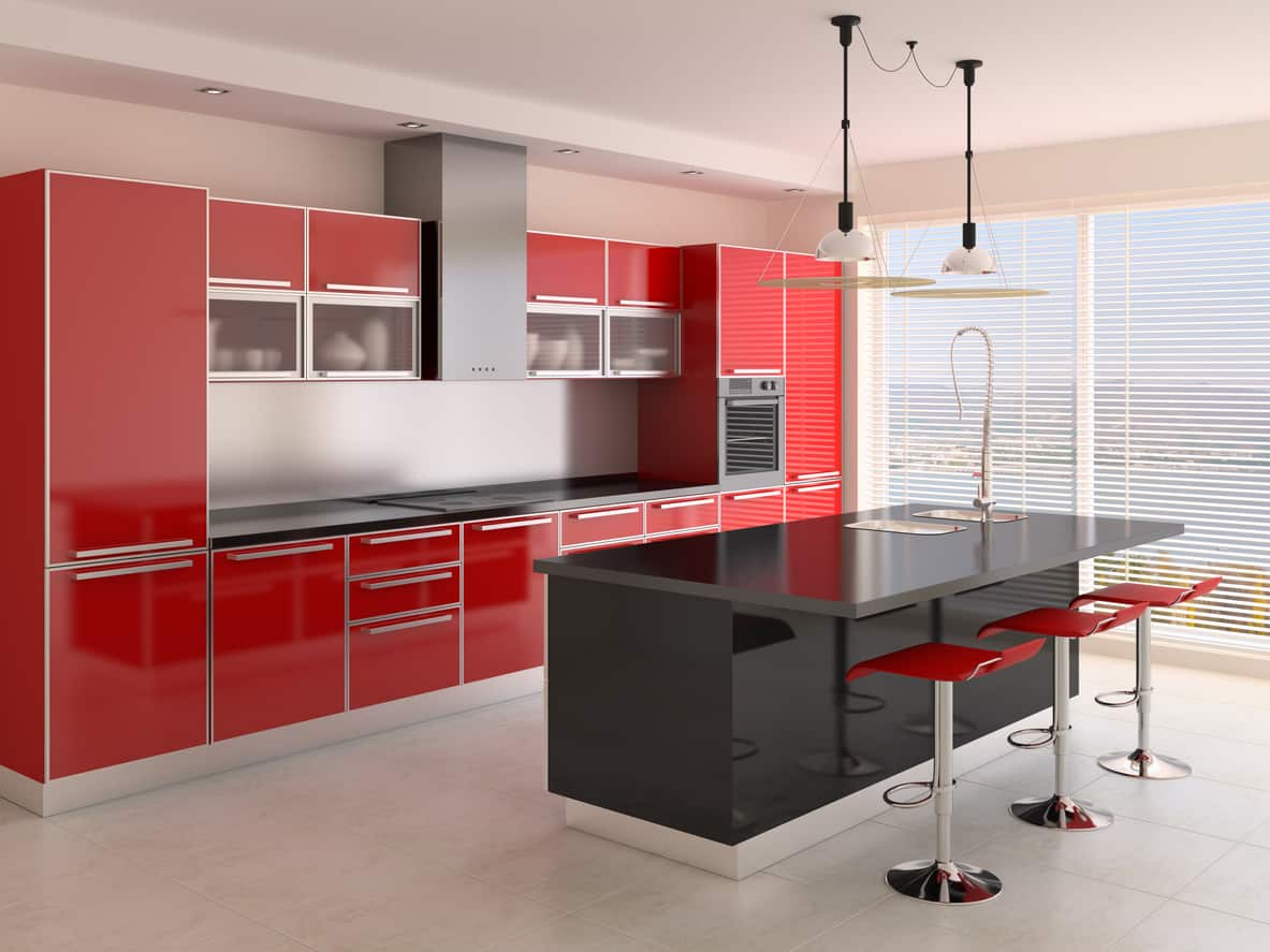 Single wall kitchen with red cabinets and black island. The red is tied back in to the scheme with modern red kitchen island stools.