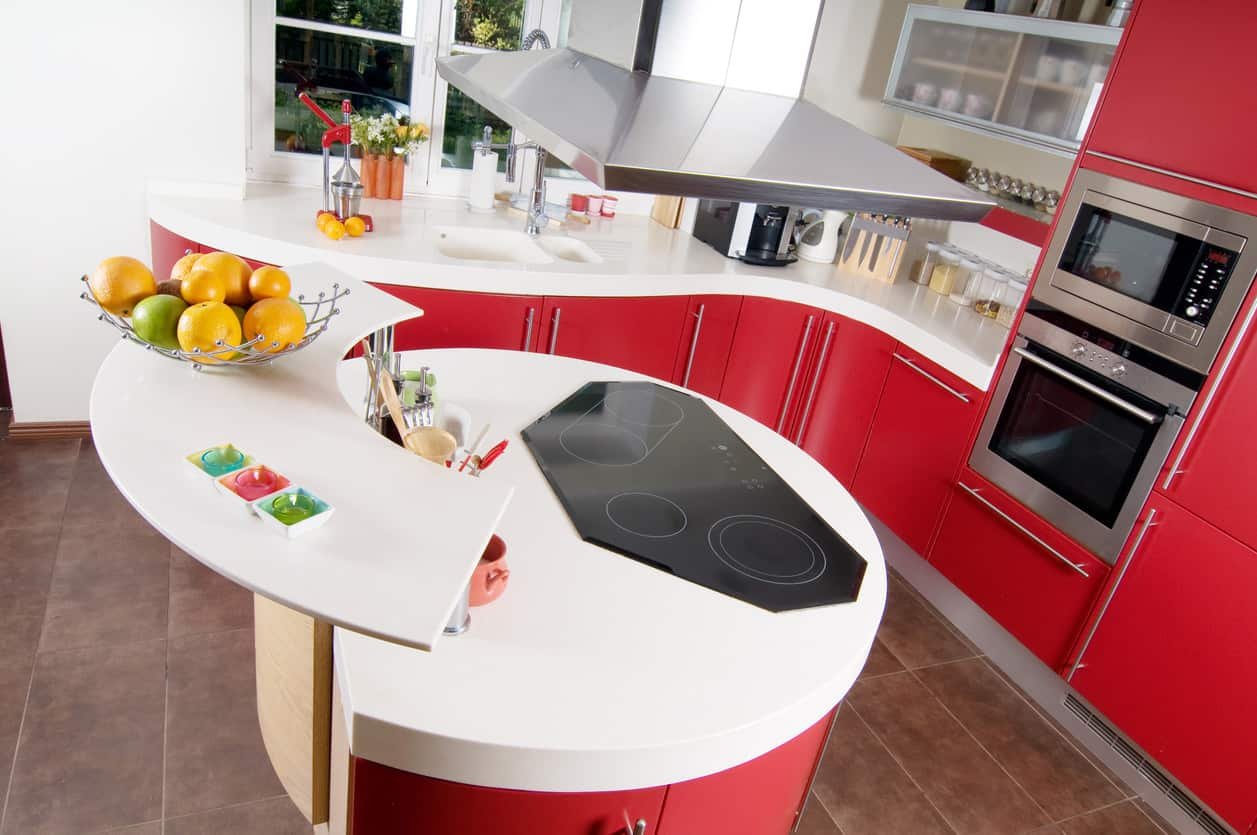 Great use of curves in this red kitchen with bright white countertops. The small round island matches the cabinets throughout the kitchen. This is a fun and whimsical kitchen design.