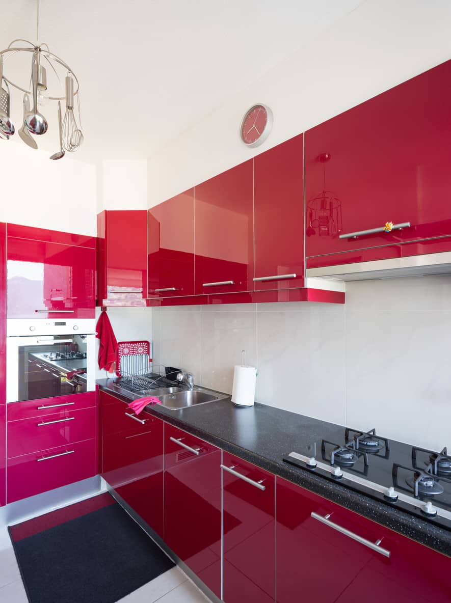 Close Up Photo Of A Small L Shaped Red Kitchen With Black Countertops