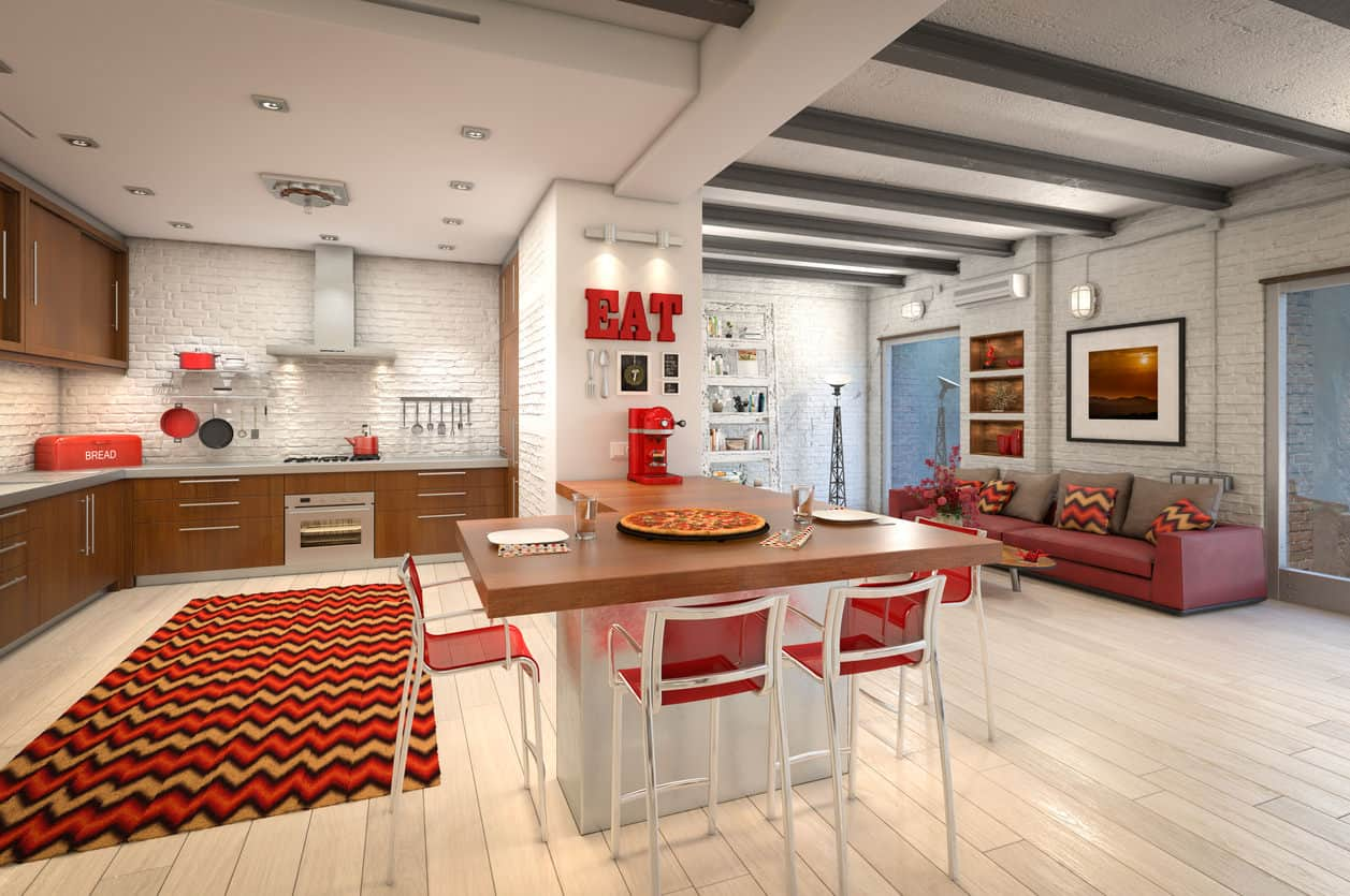 Example of a red kitchen without red cabinets. This example has some red splashes such as red island stools, red small appliances, red decor elements, red area rug and red sofa.