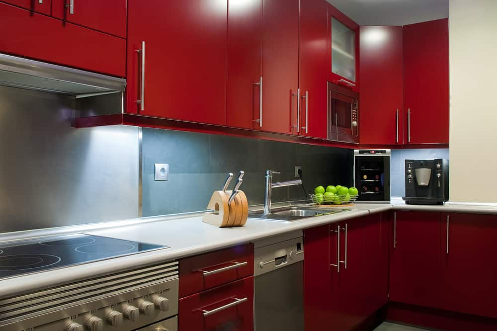 Close up of a contemporary red kitchen with chrome hardware and white countertops.