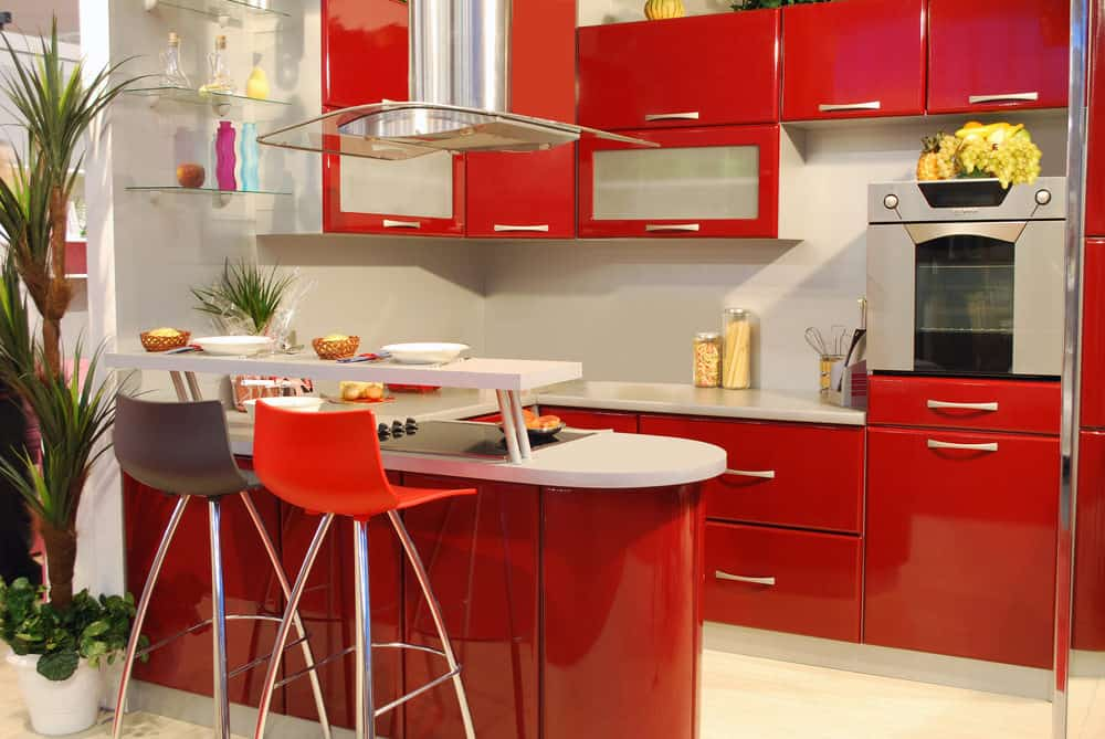 Small u-shaped apartment kitchen with all red cabinets and white countertops. There's also a white breakfast bar. There is quite a bit of glass incorporated into this design which works really well.
