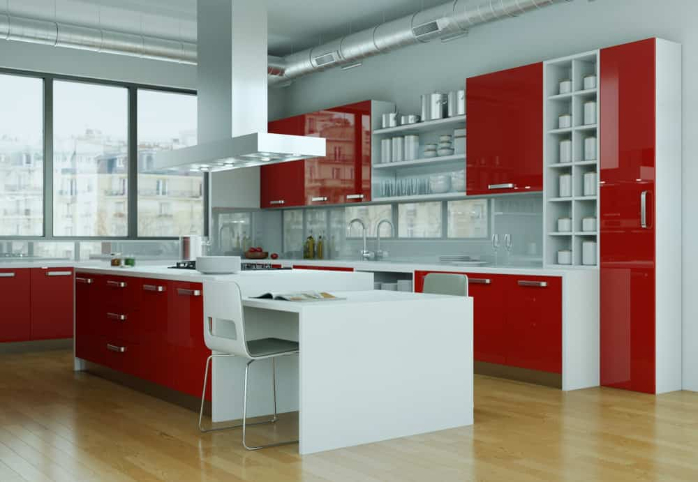 Large red and white loft kitchen. Notice how the fronts of the cabinets are red and the sides are white. The extensive white offsets the brightness of the red. I think it's done really well. You get that industrial look with exposed pipes in this renovated loft apartment.