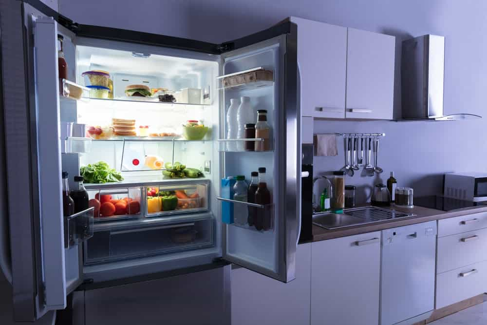 Top part of the refrigerator in the kitchen is left wide open revealing bottles of juice, fresh fruits and vegetables.