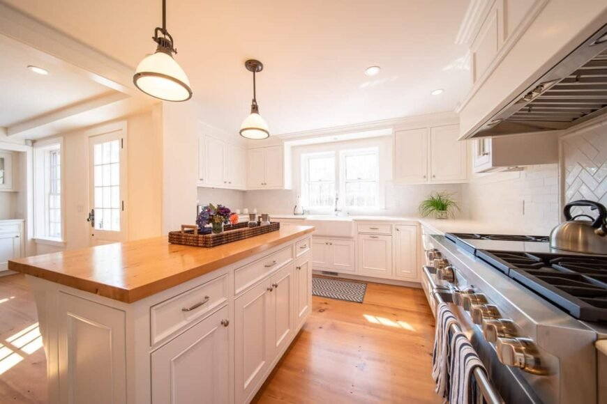 A remodeled kitchen done in mostly white with natural light wood floors and wood island surface.
