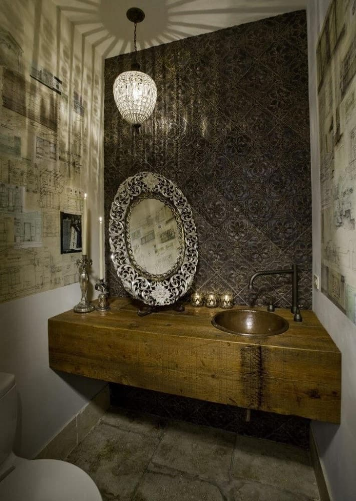 This charming Rustic-style powder room has thick wooden floating vanity that houses the brass bowl-sink and the elegant artistic mirror that leans on a stand. These are complemented by the patterned and textured backsplash tiles with a dark tone.
