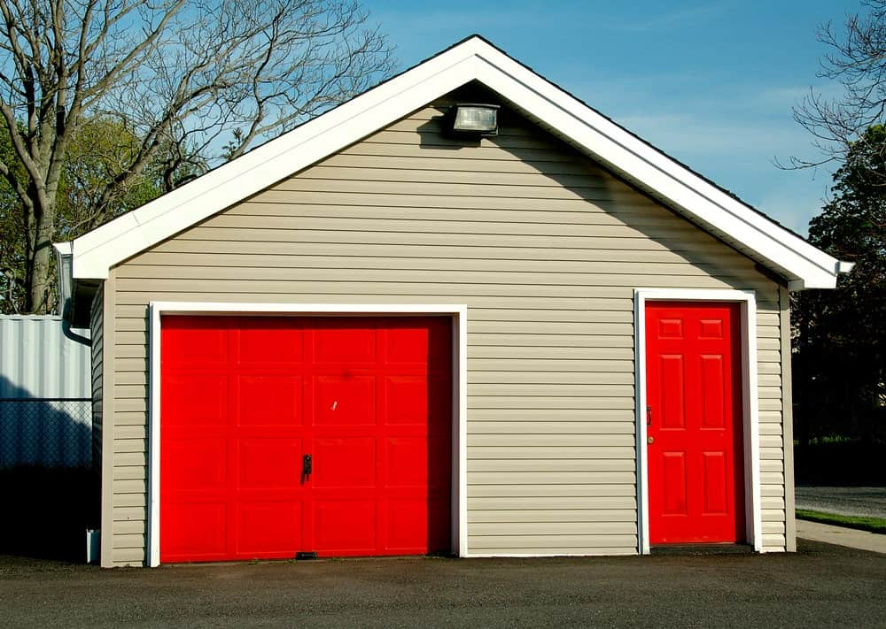 Shed garage with two red doors.
