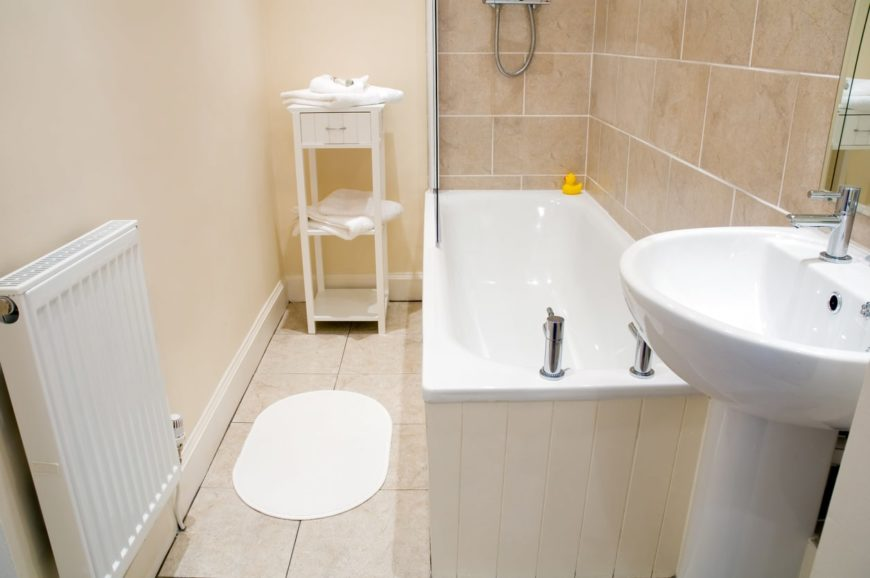 Small bathroom with a small bathtub-shower combo, pedestal sink, end table, and heater.