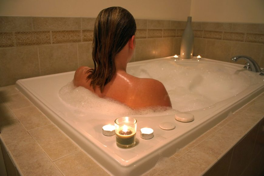 Back view of a woman soaking in the tub with scented candles.