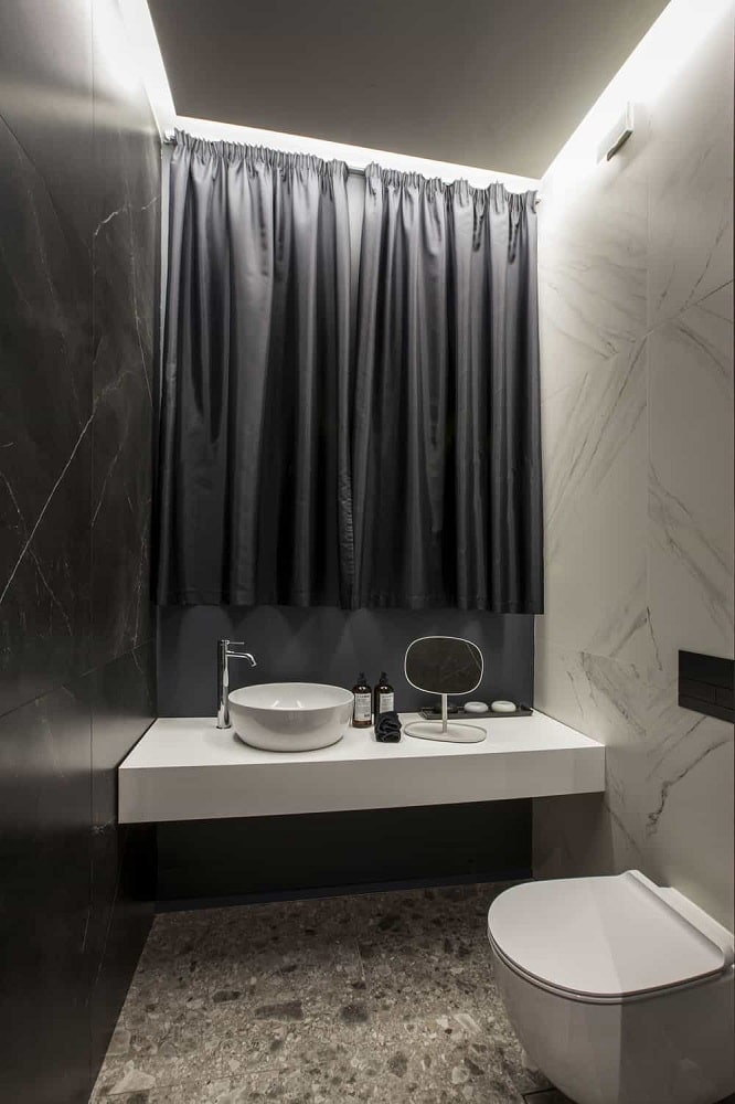 This is a simple modern black and white bathroom with a black wall across a white wall that houses the modern toilet and the white floating vanity contrasted by the black curtains above.