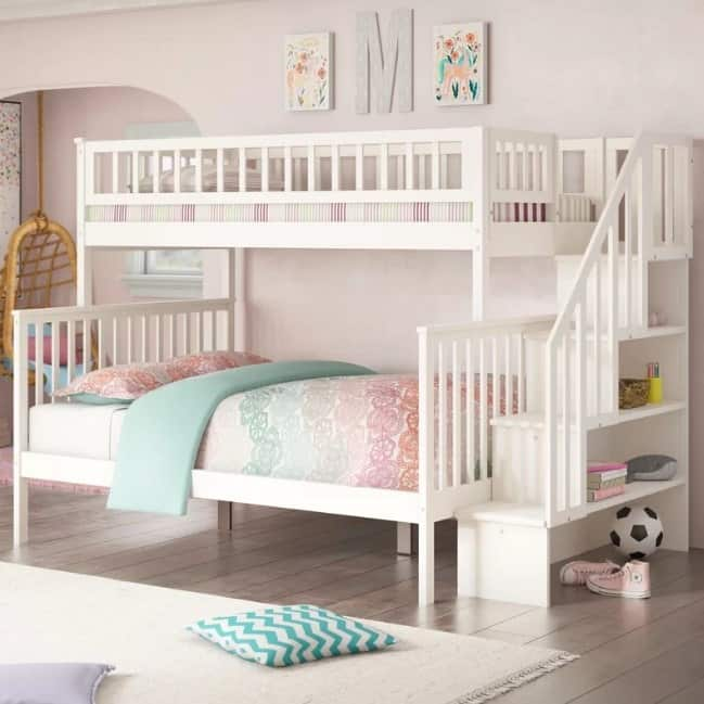 White bunk bed with stairs and built-in storage.