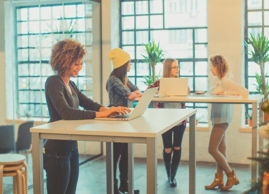 Four ladies working at a standing desk.