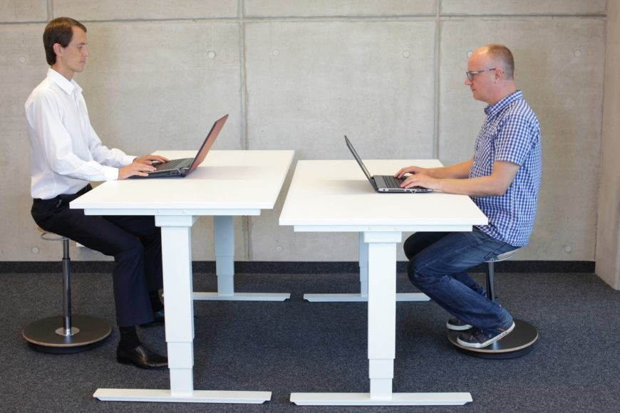 Two men opposite each other working on their laptops while sitting on stools.