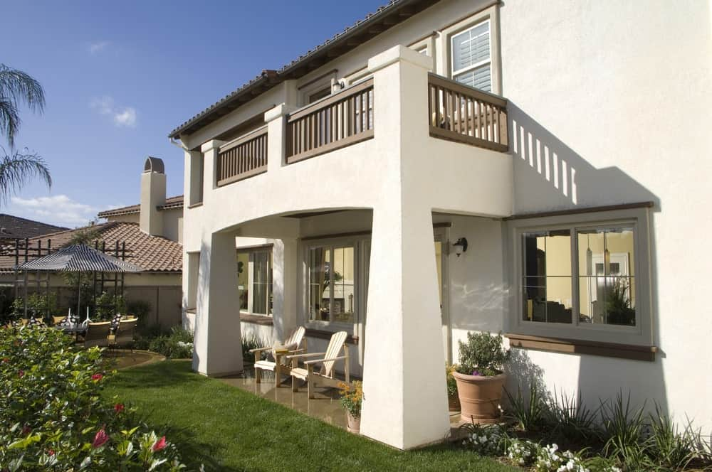 Landscaping and exterior view of a home with white stucco.