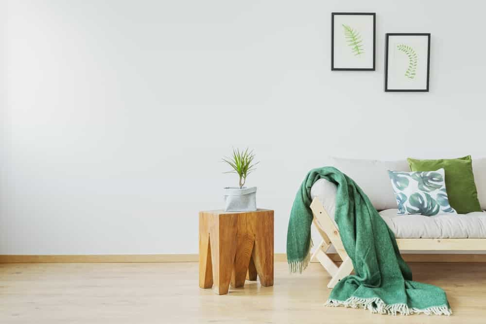 Stylish stump side table with a small potted indoor plant beside the living room sofa with throw pillows and blanket.