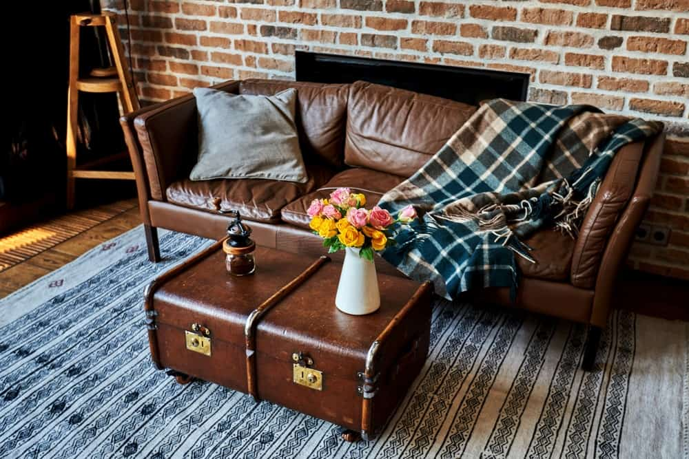 Urban-chic living room with exposed brick wall and and a matching leather sofa and suitcase coffee table.