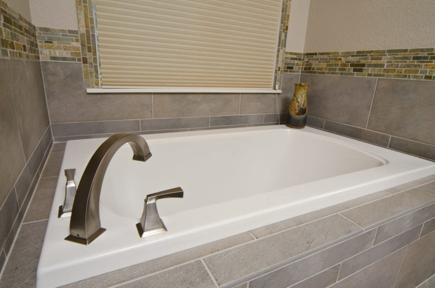 Sunken bathtub with wall tiles.