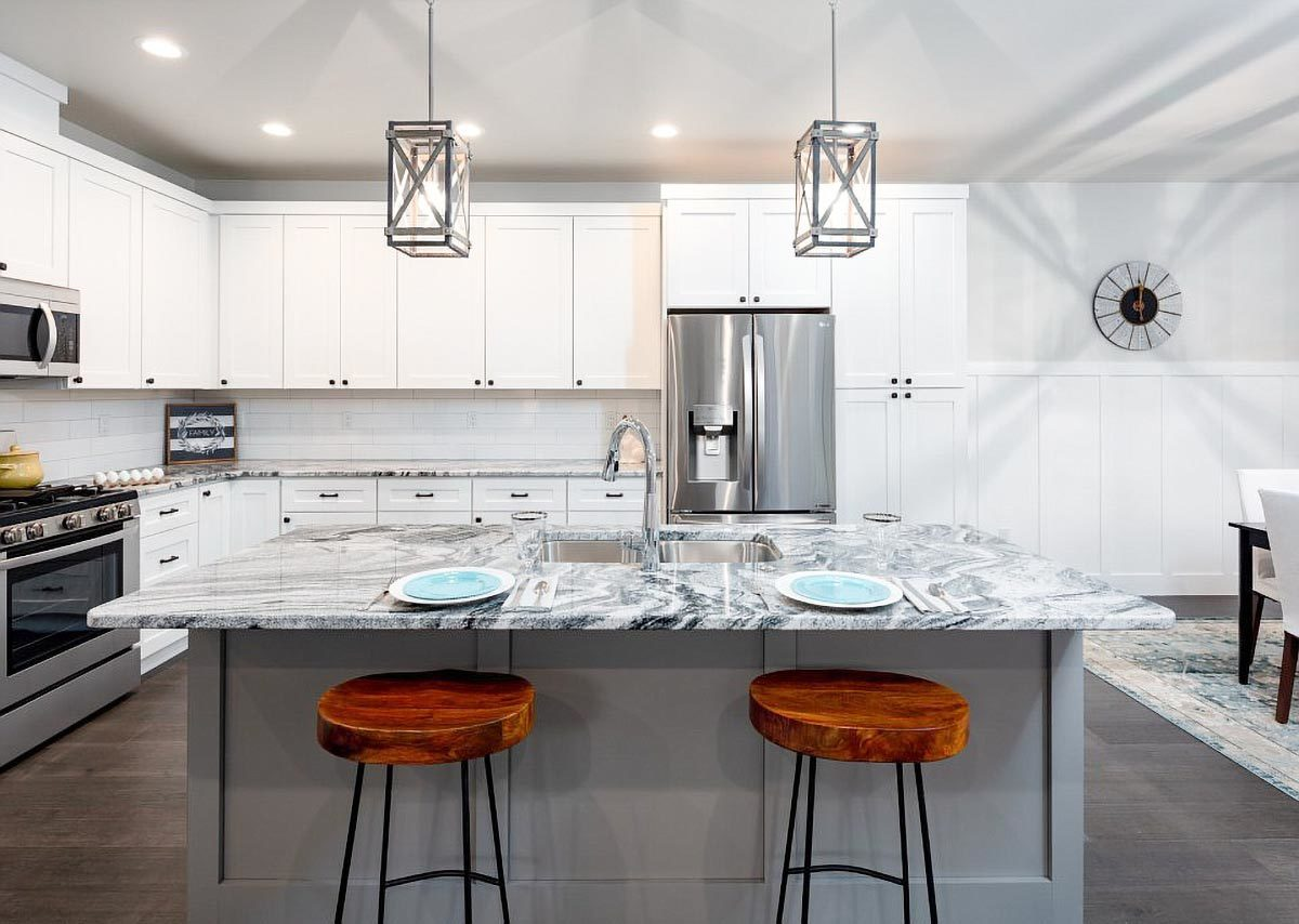 This kitchen showcases white cabinetry, marble countertops, stainless steel appliances, and a multi-use island well-lit by a couple of eye-catching caged pendants.