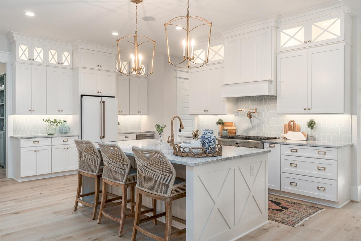 Light wood elements combine to the white scheme of this kitchen to bring a fresh and cozy look. Brass accents from the hardware and lighting add elegance to the area.