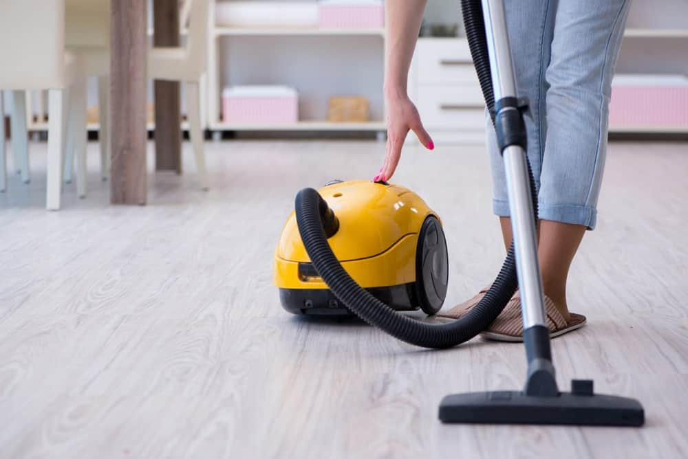 A vacuum cleaner used for cleaning the light wood flooring.