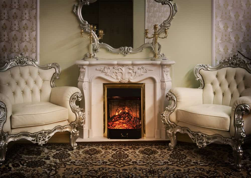 Victorian style fireplace mantel flanked by a pair of tufted armchairs.