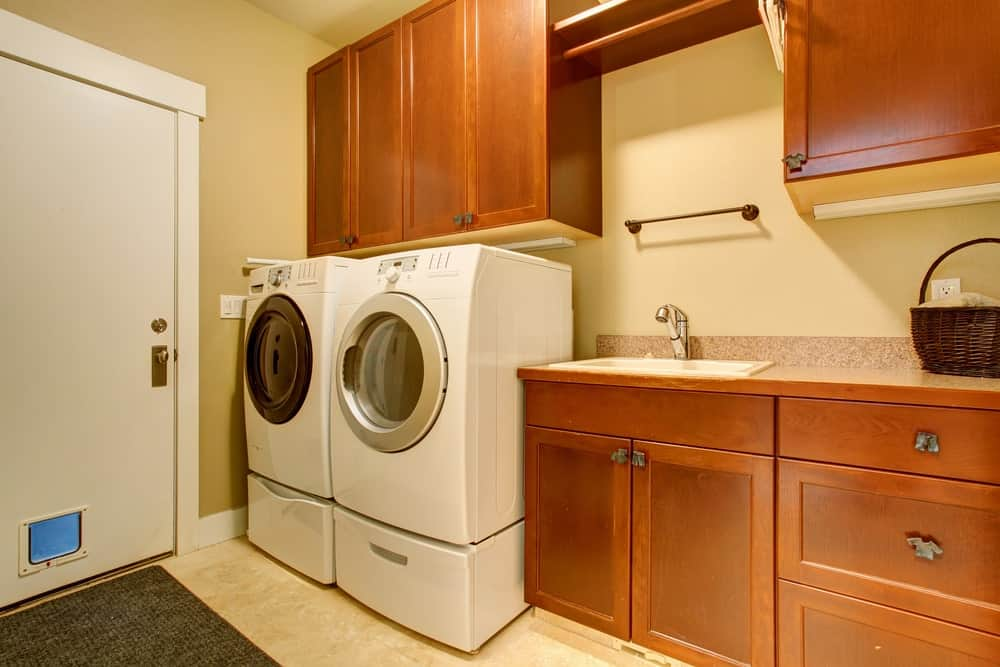 Modern laundry room with white front load washer and dryer with pedestal.