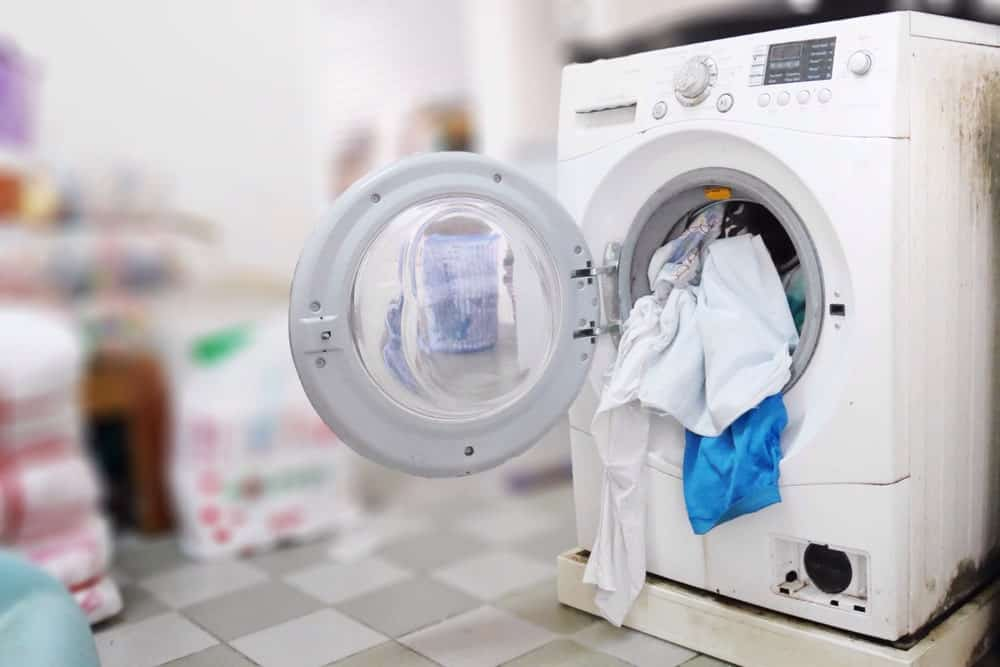 An open washing machine with laundry clothes spilling out.