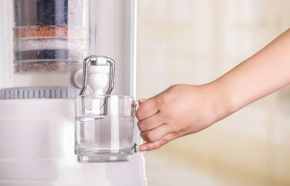 Getting a glass of water from a water filter.