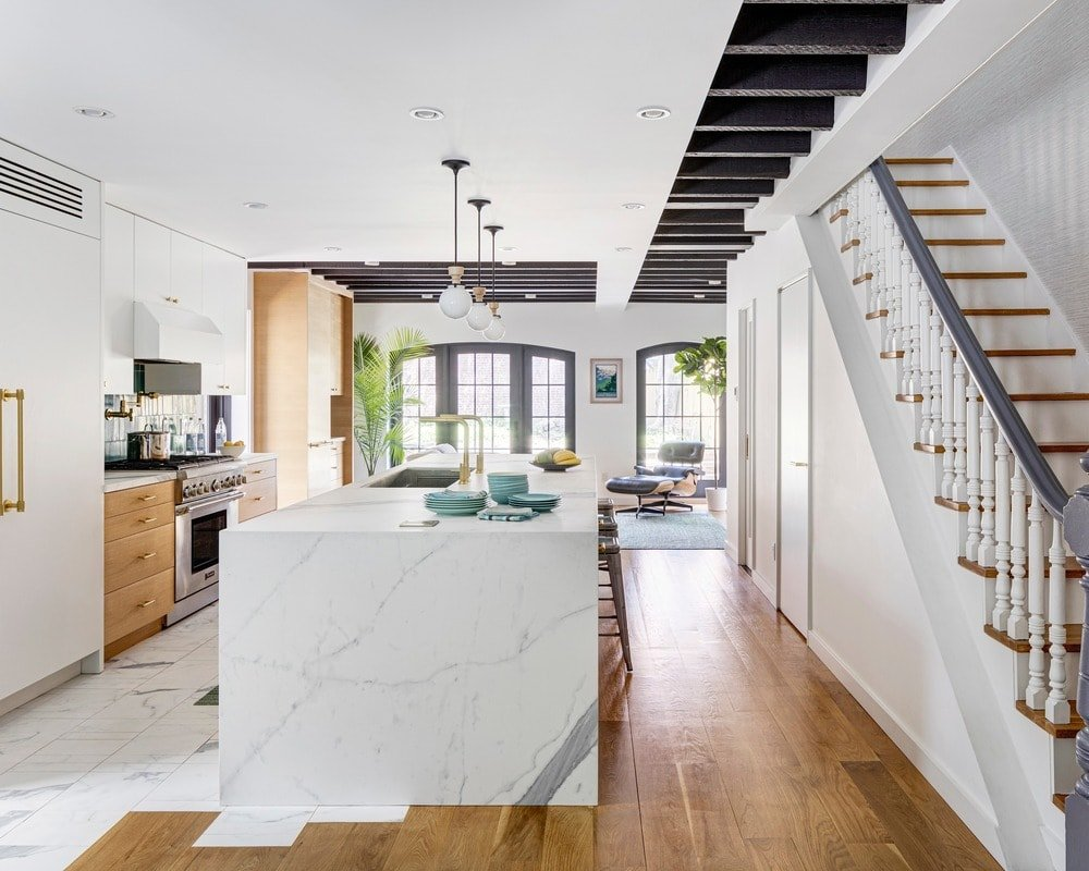 This beautiful and simple white kitchen has half the hardwood flooring of the hallway and half the white marble flooring for the cooking area. This match up is mirrored by the white marble waterfall kitchen island and the wooden cabinets of the kitchen peninsula.