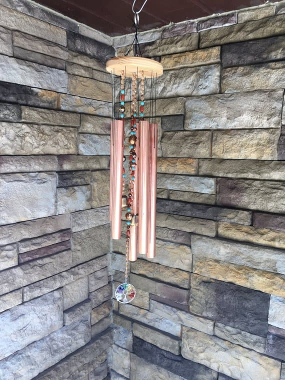 Wind Chimes with stone tile walls as background.