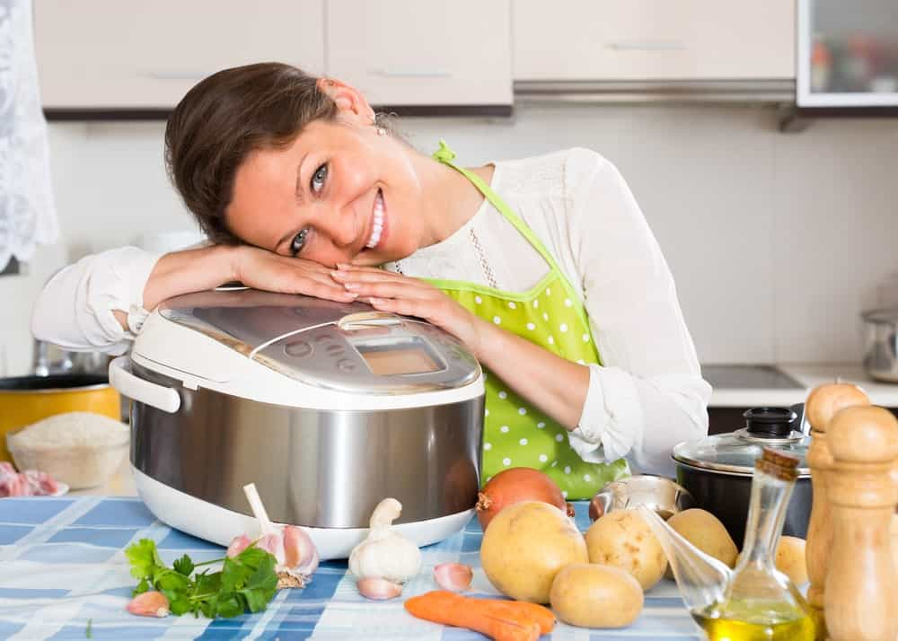 Woman smiling as she rests on a crockpot on a kitchen countertop filled with potatoes, garlic, oil, etc.