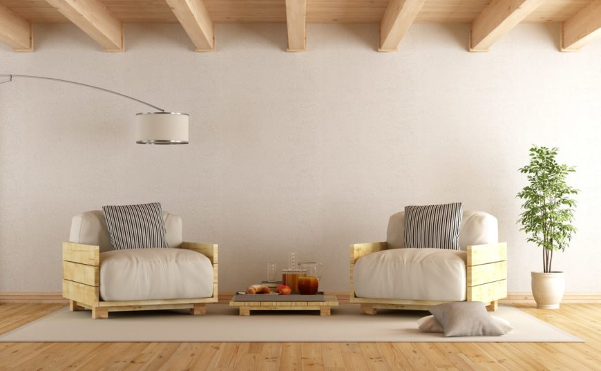 Stylish interior with wooden plank ceiling, floor lamp, an indoor plant, and a pair of wooden arm chairs with a low coffee table with rug on wooden flooring.